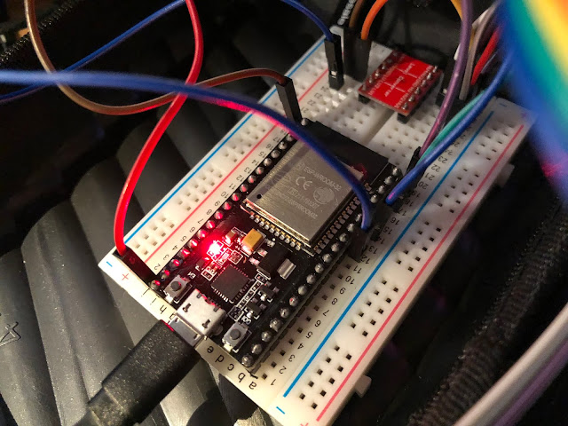 an ESP32 prototype board and a small red level-shifter board on a breadboard, with jumper wires running all over the place