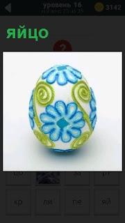 Разукрашенное обычное яйцо на белом фоне , причудливые узоры на боках с вензелями
