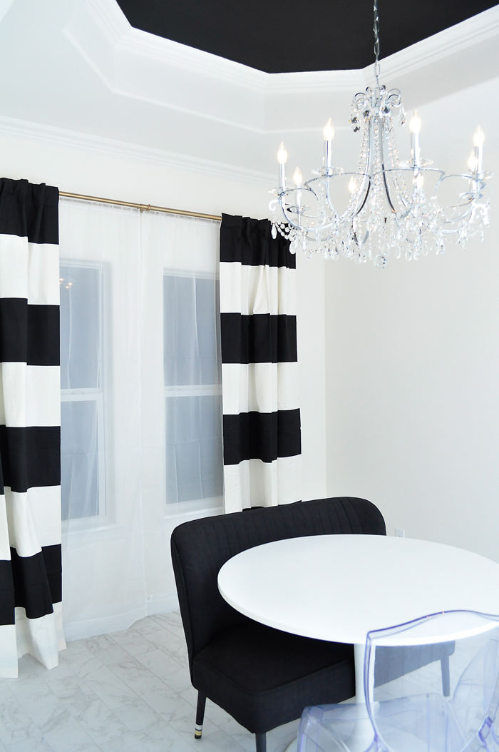 Black and white striped curtains in a dining space with a large crystal chandeilier