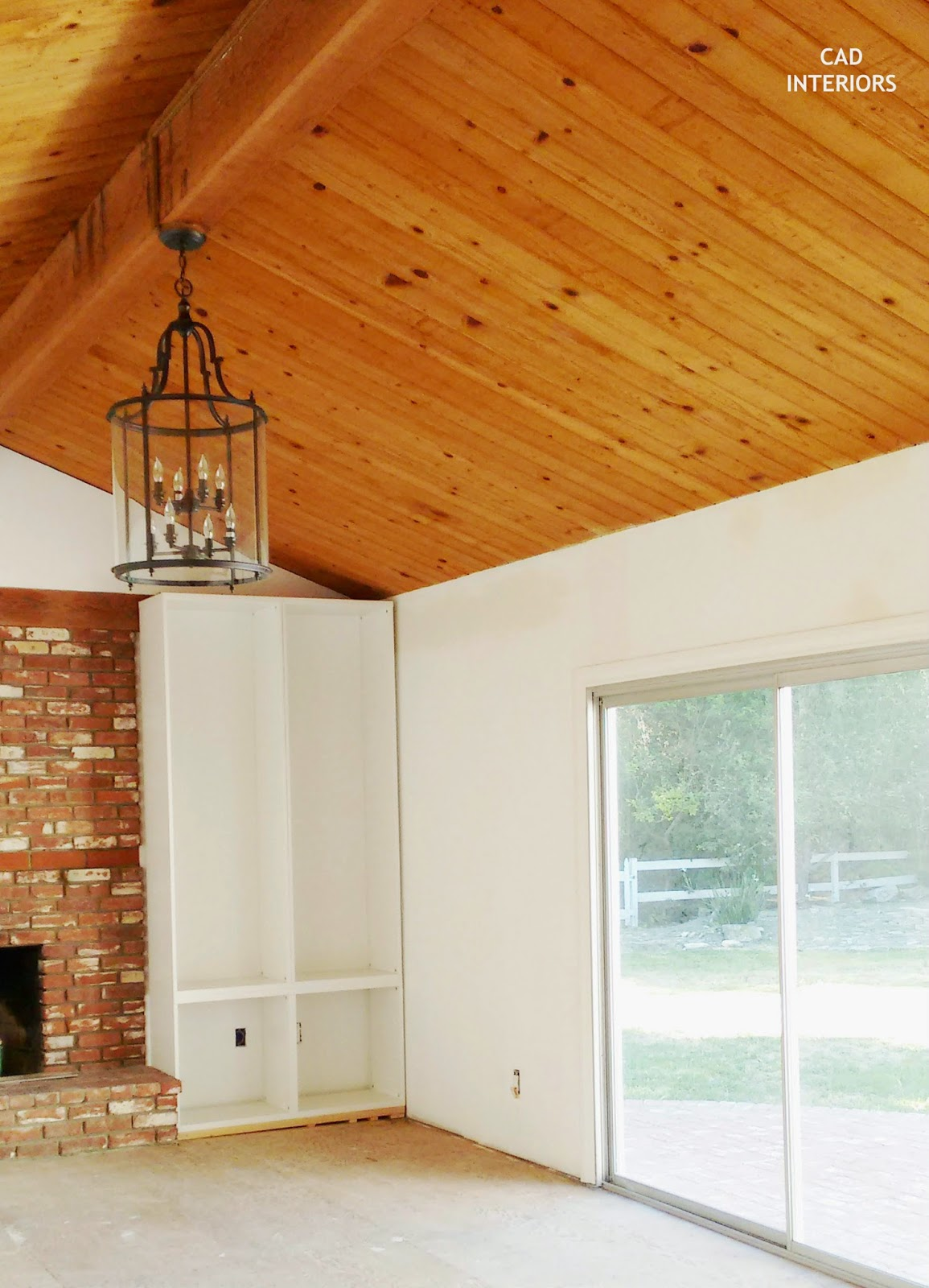DIY built-in cabinets brick fireplace pendant light fixture wood ceiling beams