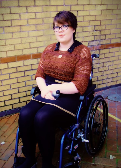 Young woman with short brown hair, glasses, orange kit top, purple dress and purple stockings, sitting in a manual wheelchair