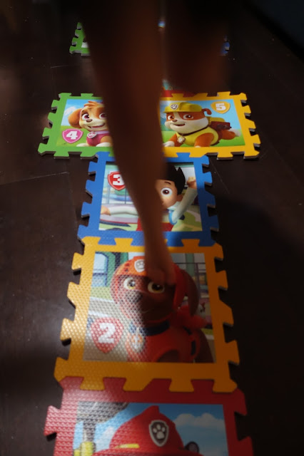 A blurry pair of legs playing hopscotch on the Paw Patrol playmats