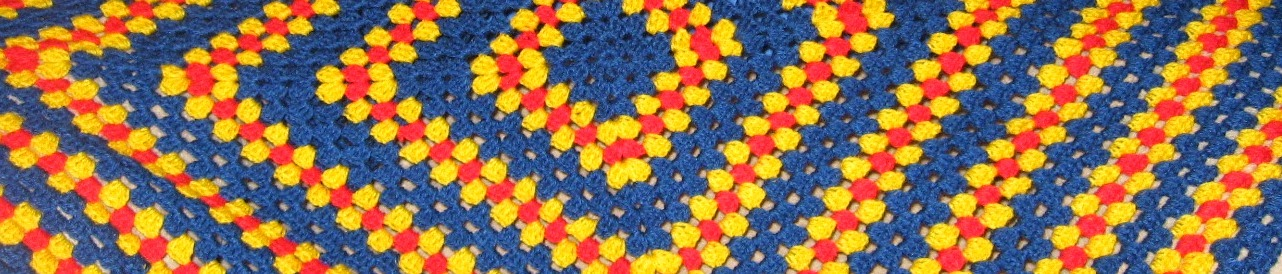 Close up of a blanket-sized granny square in blue, yellow and red.  The pattern repeat is three rounds of blue, one of yellow, one of red, one of yellow, (start again) three rows of blue etc.