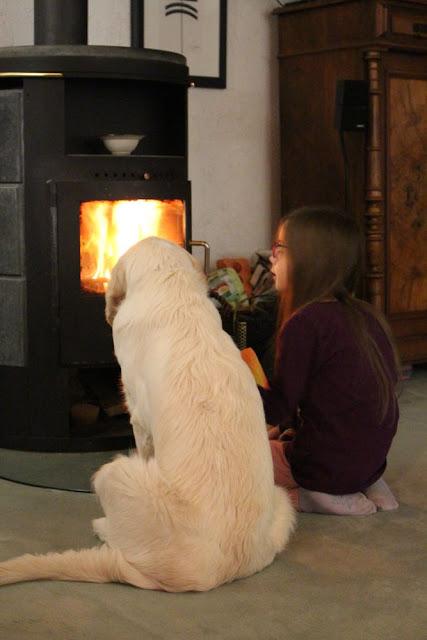Hund und Mädchen hocken vor dem Ofen