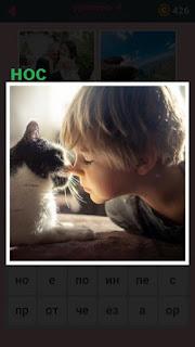 кошка приблизила свой нос к мальчику в лицо