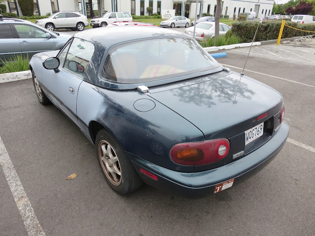 Faded Mazda Miata in need of paint & collision repairs