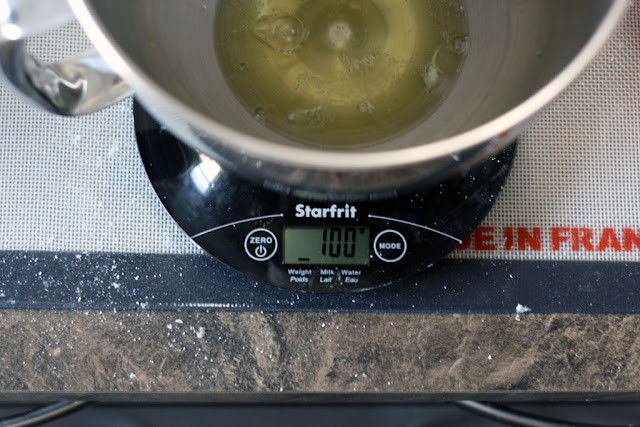A metal bowl containing only egg whites on top of a scale displaying 100 grams.