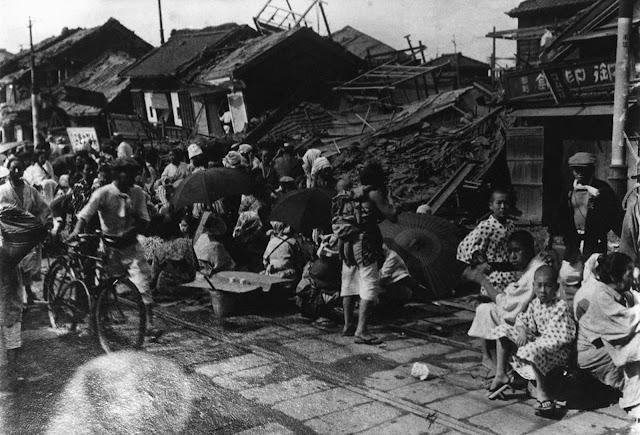 Muitas pessoas sentam-se na estrada de ferro dos bondes em frente às casas destruídas no Japão em 1923, após um terremoto.  Felizmente, esta área não sofreu incêndio.