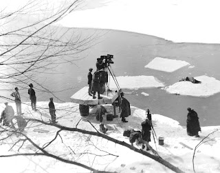 A photograph of a film crew working at a snowy river's edge.