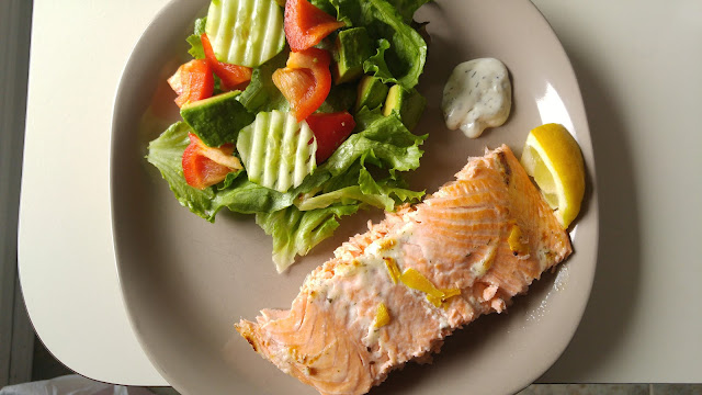A plate with dill baked salmon and vegetable salad on the side.