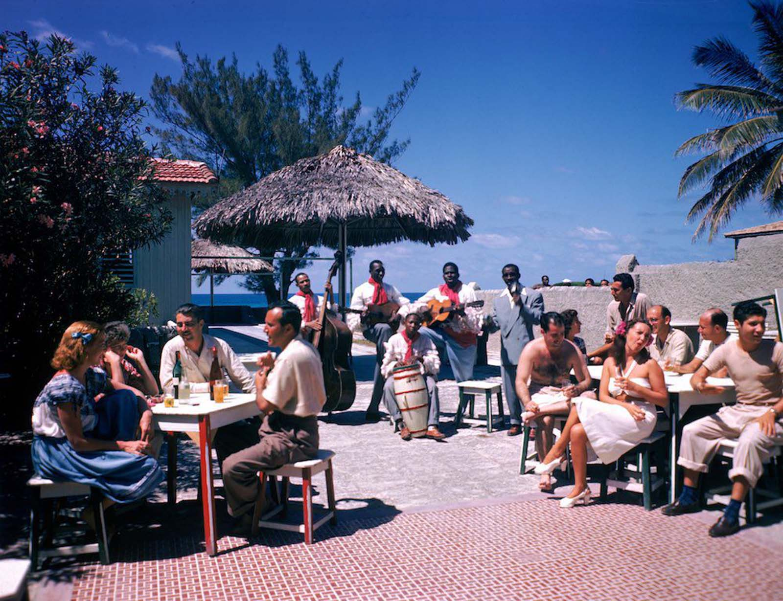 Guests sit at outdoor tables in the Kastillito Club and talk together while a band performs in Varadero, Cuba. 1946.