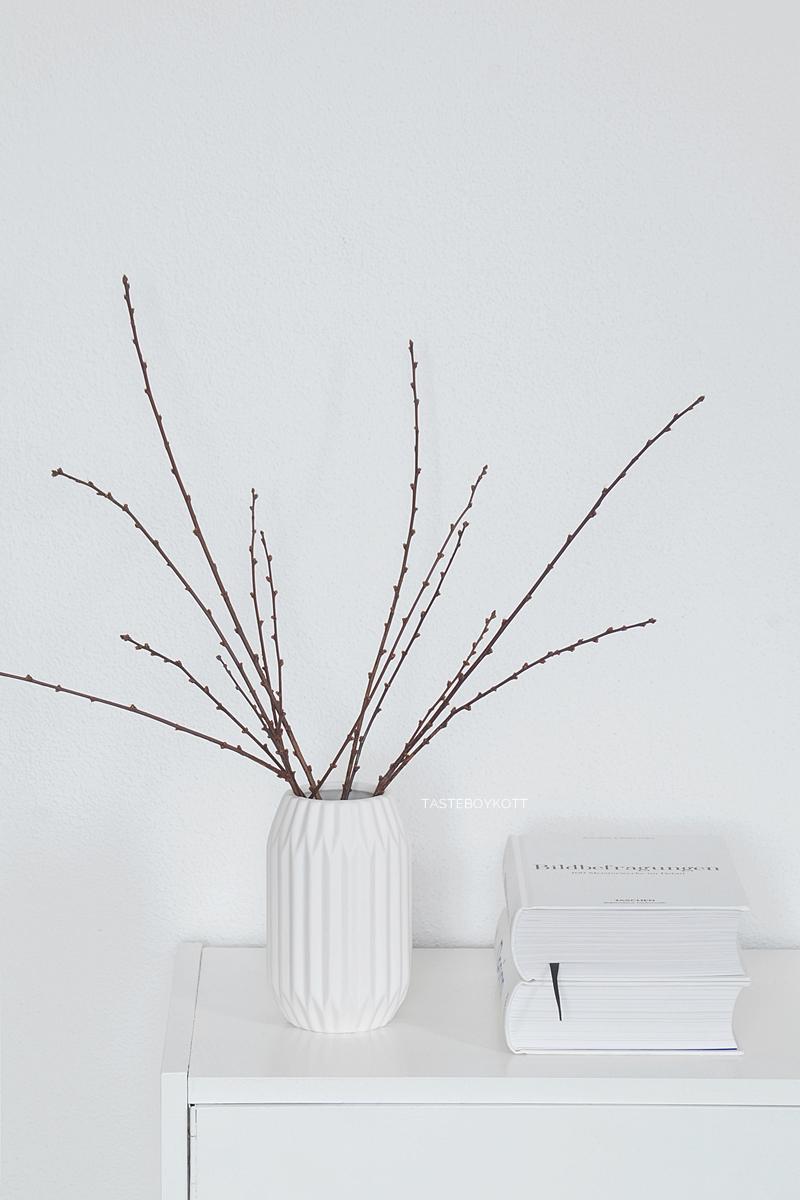 Weiße Vase in Origami-Optik mit Zweigen als schlichte skandinavisch-moderne Winterdeko. Tasteboykott.