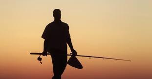 Foto de um pescadoer indo a praia com uma vara na mão