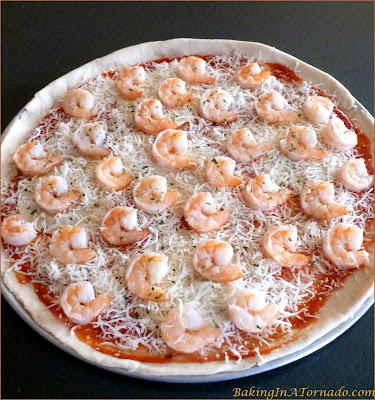 Rosemary Infused Shrimp Scampi Pizza: A crunchy rosemary infused pizza crust topped with homemade marinara, melted cheese and scampi flavored shrimp | Recipe developed by www.BakingInATornado.com| #recipe #pizza #shrimp