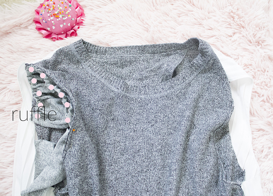 grey sweater with ruffle piece pinned to it