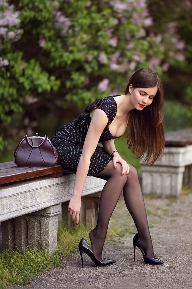 Czarna obcisła sukienka w kropki, czarne rajstopy i skórzana brązowa torebka na bigiel