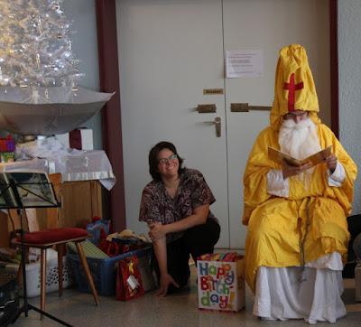 das Bild zeigt rechts den Nikolaus in goldener Tracht