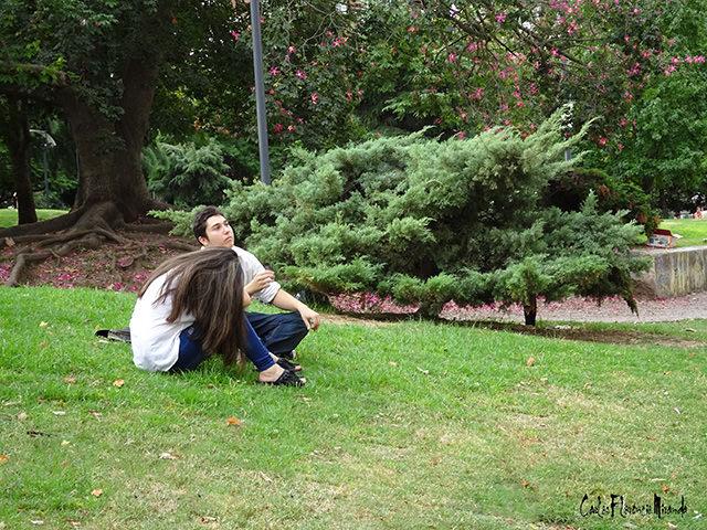 Una pareja sentada en el césped del parque.