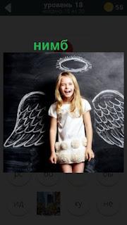 на доске нарисован нимб и крылья среди которых стоит девочка