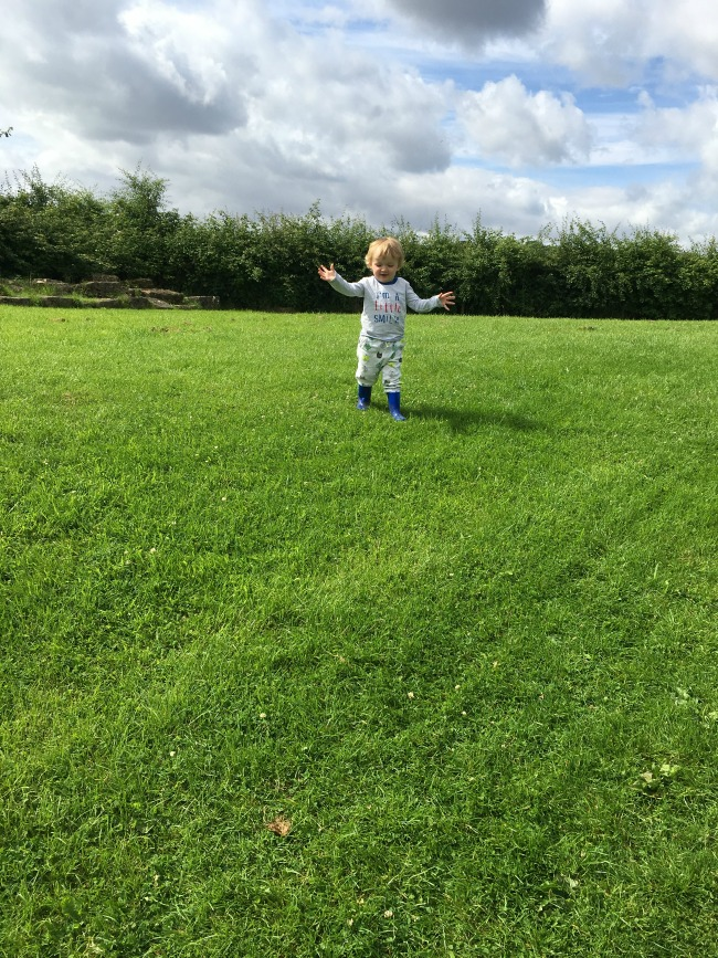 Caerleon-the-roman-fortress-of-isca-a-toddler-running-with-arms-open-to-camera