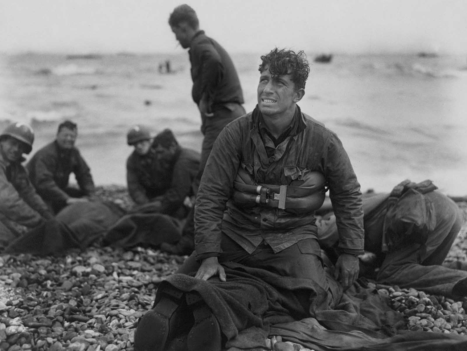 American soldiers on Omaha Beach recover the dead after the June 6, 1944, D-Day invasion of France.