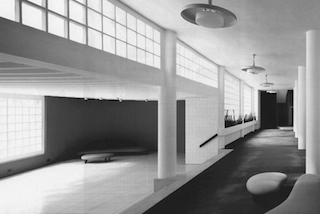 Black and White photo of modernist entry lobby with glass bricks, concrete piers and title floors