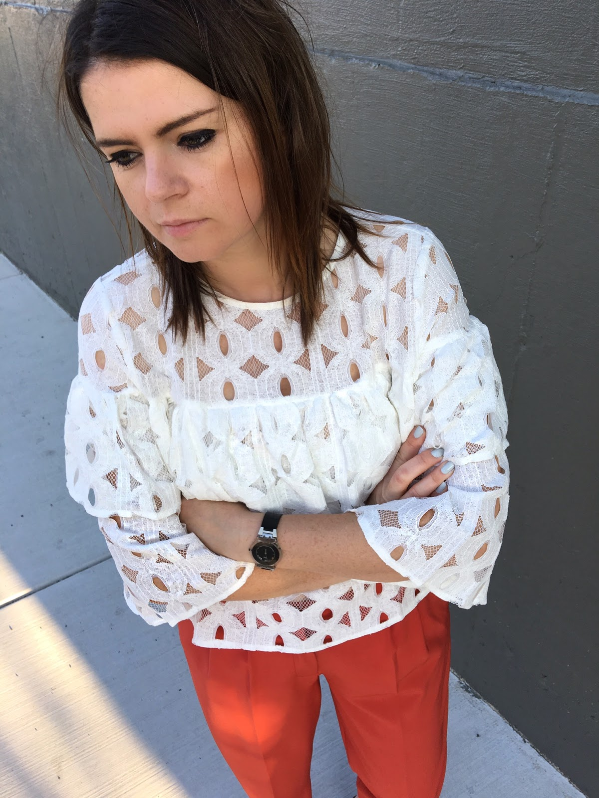 White ruffled blouse & rust color pants