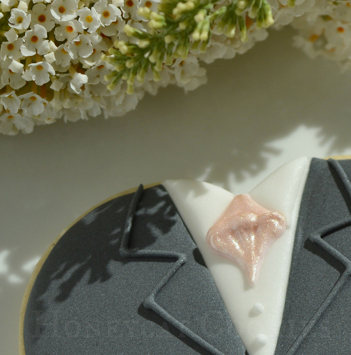 Close up of lustre painted pocket handkerchief on groom heart decorated cookie, by Honeycat Cookies