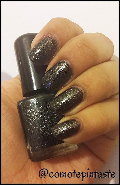 Muestro el esmalte en mis uñas. Es negro con glitter plateado