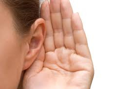 Mulher com a mão na orelha para ouvir melehor