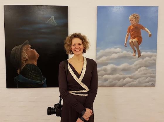 Malene Klint vejlby foran to oliemalerier, hvor hendes egne drenge er modeller.
