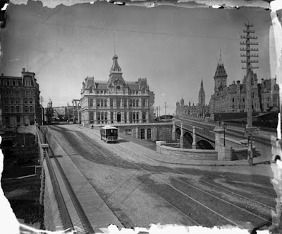 Photo from 1880 taken from the east side of the Sappers' Bridge looking west along Sparks and Wellington streets, showing the diverging Sappers' and Dufferin bridges, between them across the canal the elaborate Post Office building, and on the far side of Wellignton Street the east and west departmental buildings on Parliament Hill. Along the surface of the bridge there is a plank sidewalk, then dirt roads with two sets of inlaid rails, one of which carries a horse-drawn streetcar. In the middle of the two bridges is a continuous wall which curves around and which has a plank sidewalk doing the same. At the apex of thsi curve is a utility pole with eight rows of 4-6 insulators carrying telephone lines.