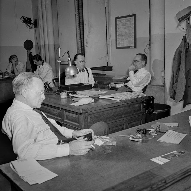 In the bullpen. The assistant managing editor sits in the foreground while the managing editor and night managing editor confer in the background.