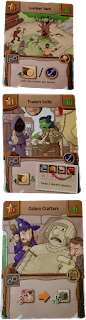 Three cards: the Lumber Yard with a picture of a treefolk fighting three other characters, with icons indicating that the card lets you gain one wood for each anchor you possess; the Trader's guild, with art showing a cloaked figure holding a chicken trying to trade with a goblin leading a giant chicken, and icons indicating that it lets you gain one wood and swap the places of two goods on the market on the central play mat; and Golem Crafters, with art showing a wizard and a stonemason building a large statue, with icons indicating that it allows you to convert three meat into five stone.