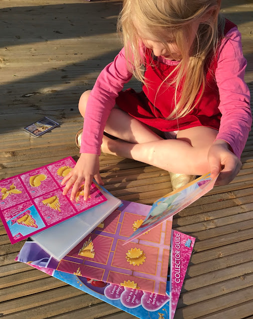 A young girl look at the starter pack including a small pack of cards, a sheet of stand up cards, a clear plastic binder and a couple of folded up A4 sheets of paper