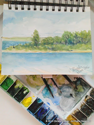 Watercolor sketch done at the lake.  Travel palette holds the watercolor mixes.