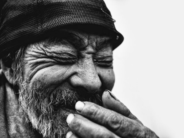Beautiful black and white photo of old man closing his eyes and laughing