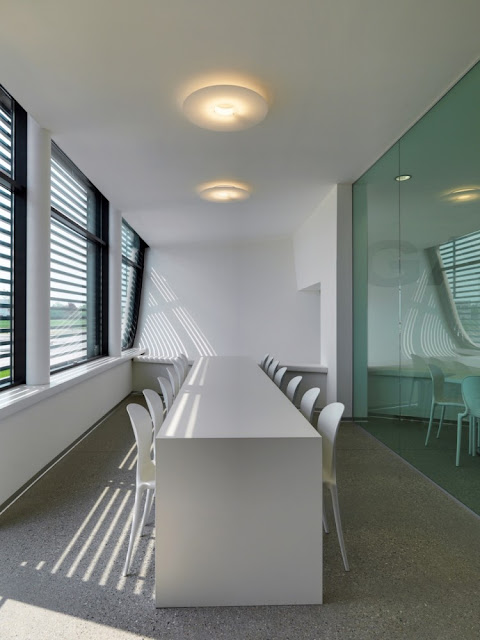 Photo of white interior and the room with table and the chairs at Gazoline Petrol Station by Damilano Studio Architects