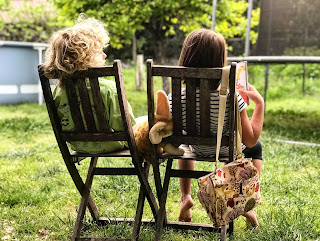 Two children facing away from the camera on to wooden chairs on a green lawn.