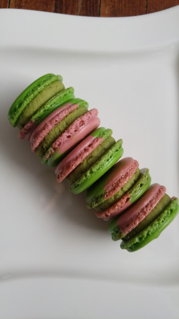 A plate of raspberry matcha macarons stacked sideways.