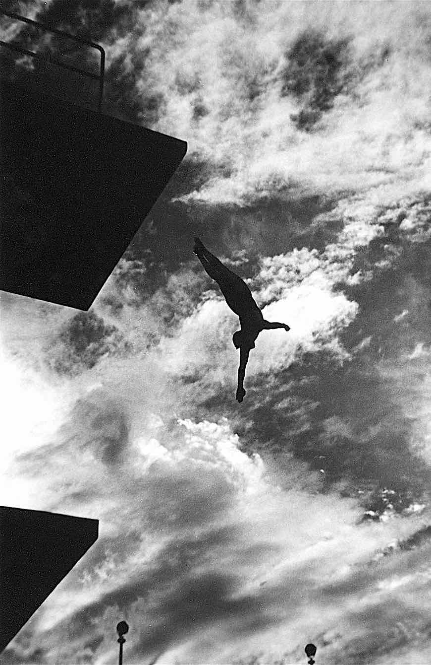 a Leni Riefenstahl photograph at the 1936 Olympics, a high diver in silhouette