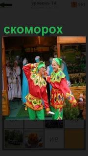 Девушка и парень в наряде скоморохов танцуют шуточный танец около дома
