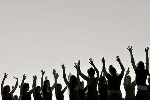 Un grupo de mujeres alzan sus manos al cielo