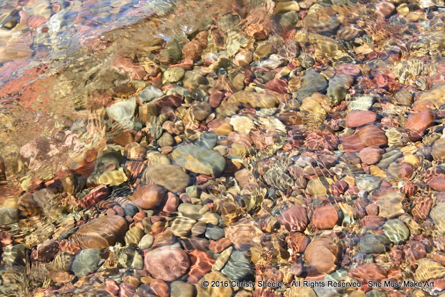 Water flows over colorful pebbles in the shallow water at the shore's edge.