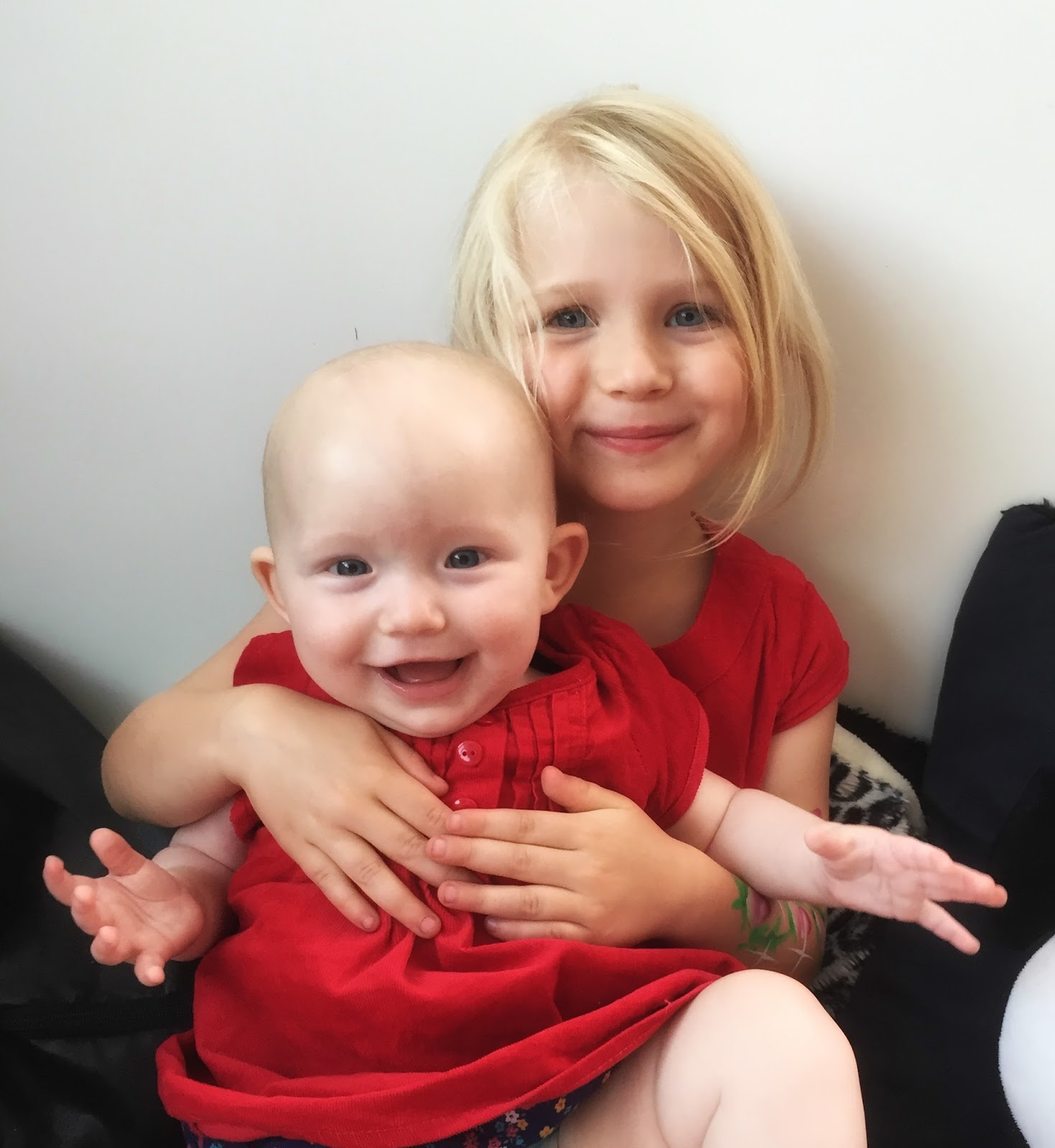 Two girls in red dresses. The older girl (M) is cuddling the baby (Little) who is smiling