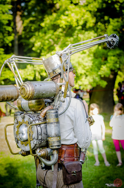 Steampunk man wearing weird gadget, contraption backpack with hand and doll's head