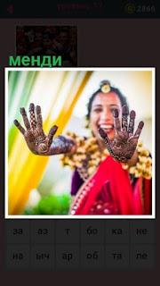 женщина показывает свои руки, на которых сделано менди
