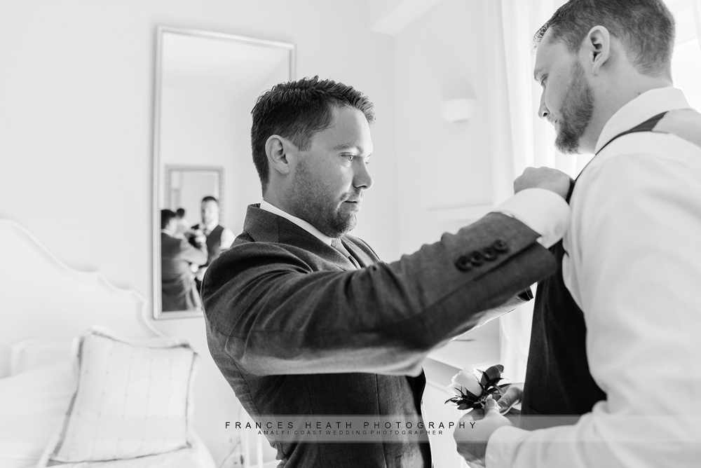 Groom and bestman putting on boutonnieres