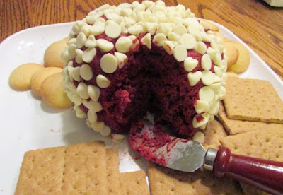 red velvet cheese ball coated in white chocolate chips with vanilla wafers and graham crackers for enjoying