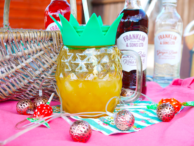 pineapple shaped drinking glass on a pink table, surrounded by glass bottles of franklin and sons drinks, and fruit lollipops